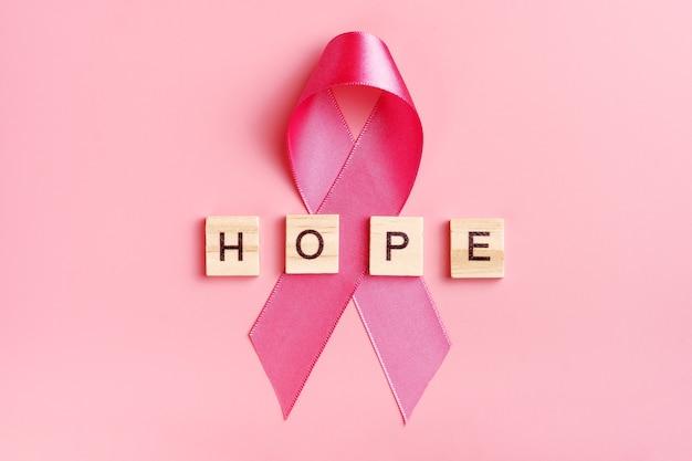 Nastro rosa e lettere in legno con la parola speranza su sfondo rosa.