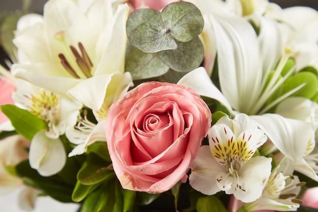 La rosa rosa e la disposizione dei fiori si chiudono sullo sfondo.
