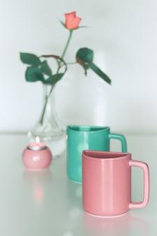 Fiore rosa rosa e due tazze gemelle da tè in rosa salmone e verde menta fresca.