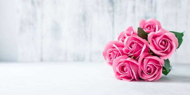 Mazzo dei fiori della rosa di rosa su fondo di legno bianco bei fiori