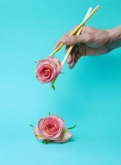 Fiori di rosa rosa in mani giovani con bastoncini un concetto minimo di idea pubblicitaria della natura