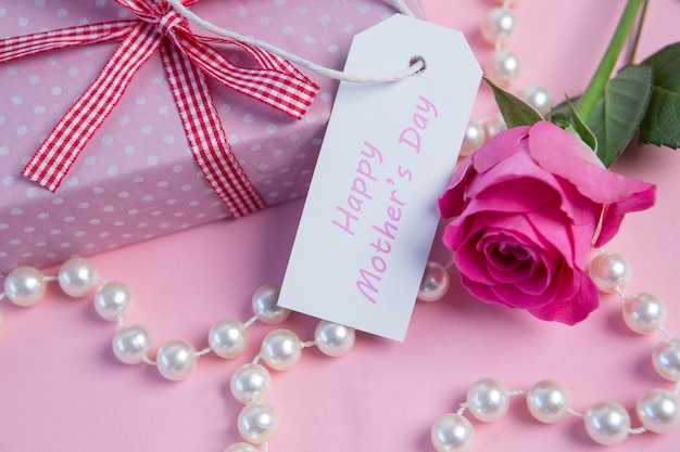 Rosa rosa con regalo e filo di perle e tag per la festa della mamma