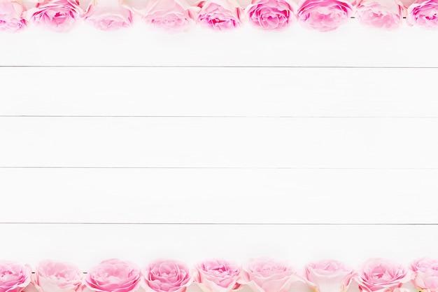 Bordo delle rose rosa su legno bianco