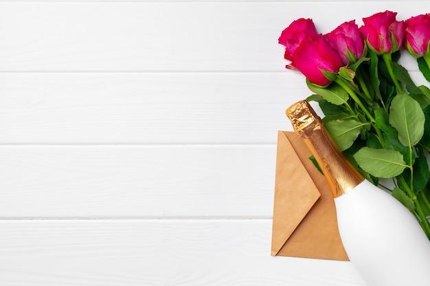 Bouquet di rose rosa, bottiglia di champagne e busta su fondo di legno bianco
