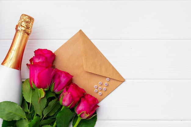 Bouquet di rose rosa, bottiglia di champagne e busta su superficie di legno bianca