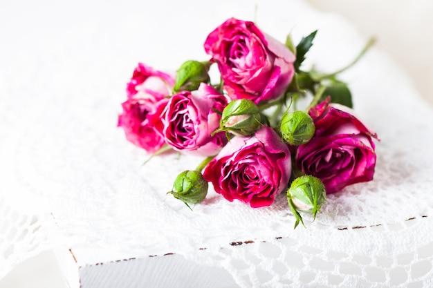 Rose rosa su centrino all'uncinetto. concetto di arredamento vintage
