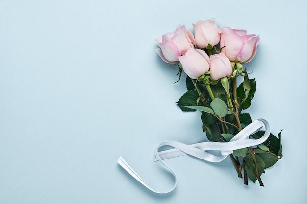Bouquet di fiori di rose rosa con nastro su un bellissimo sfondo blu. modello di biglietto di auguri con copia spazio