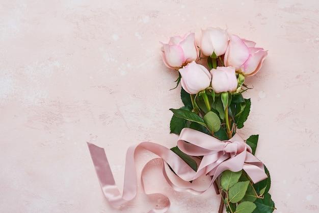 Bouquet di fiori di rose rosa con nastro su un bellissimo sfondo rosa. modello di biglietto di auguri con copia spazio