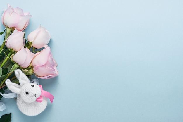 Bouquet di fiori di rose rosa con nastro e simpatico coniglietto di pasqua su un bellissimo sfondo blu. modello di biglietto di auguri con copia spazio