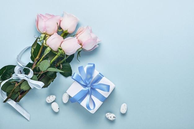 Bouquet di fiori di rose rosa con nastro, confezione regalo e uova di pasqua su un bellissimo sfondo blu. modello di biglietto di auguri con copia spazio