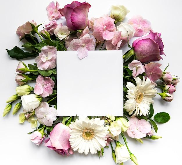 Rose rosa e fiori nel telaio con quadrato bianco per il testo su sfondo bianco