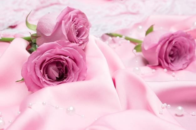 Rose rosa su tessuto di seta piegato con filo di perline bianche. sfondo romantico con fiori