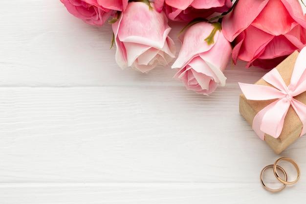 Rose rosa e fedi nuziali copiano lo spazio
