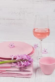 Impostazione di luogo rustico rosa con fiore di giacinto viola e tovagliolo di lino e bicchiere di vino rosato su superficie di legno bianca
