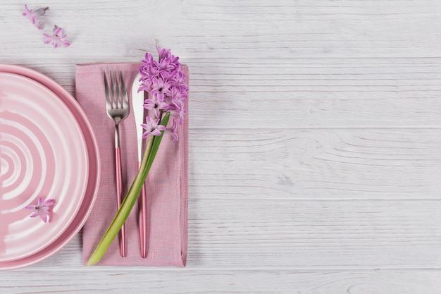 Impostazione di luogo rustico rosa con fiore di giacinto viola e tovagliolo di lino su superficie di legno bianca