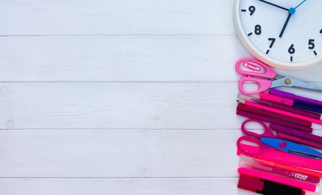 Materiale scolastico rosa e orologio su uno sfondo di legno bianco. vista dall'alto. copia spazio. istruzione e ritorno al concetto di scuola.