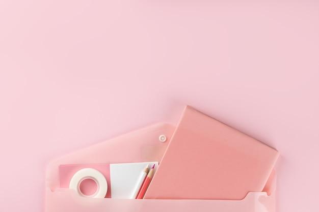 Materiale scolastico rosa su sfondo rosa. torna al concetto di scuola. vista dall'alto
