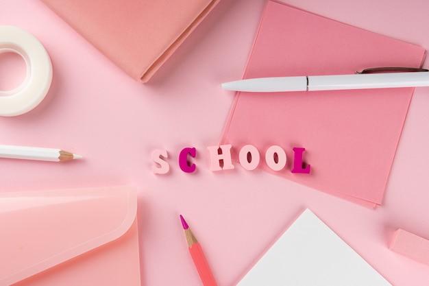 Materiale scolastico rosa e scuola di parola su sfondo rosa. torna al concetto di scuola. vista dall'alto