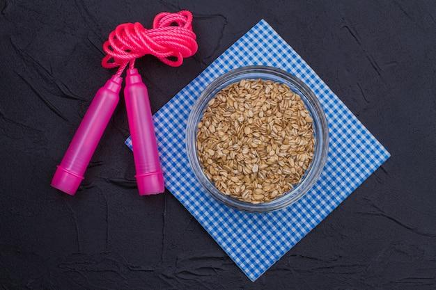 Corda per saltare rosa e porridge di avena distesi. dieta e concetto di stile di vita sano.
