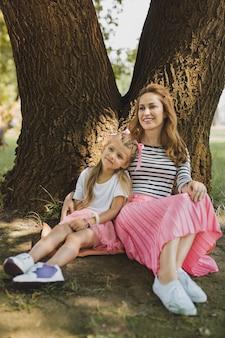 Gonna rosa. sorridente donna amorevole che indossa gonna rosa seduto vicino alla sua piccola figlia alla moda