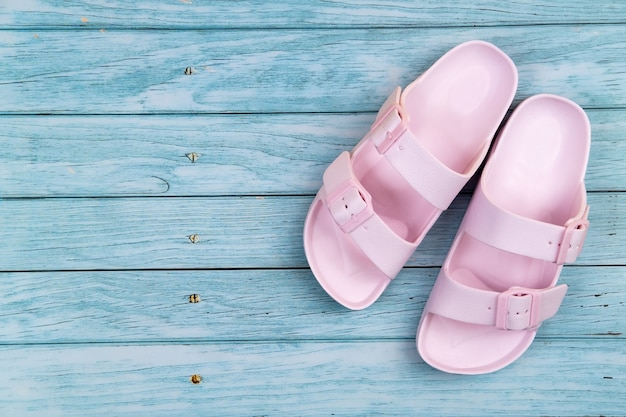 Le scarpe da ginnastica rosa stanno su un fondo di legno blu isolato