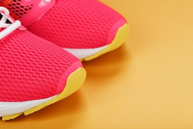 Scarpe da ginnastica rosa su sfondo giallo con spazio libero. vista dall'alto, concetto minimalista
