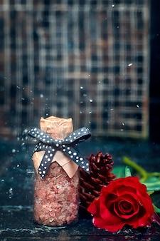 La bottiglia rosa del sale della stazione termale con la rosa rossa sul pavimento di ceramica con bella pioggia cade la priorità bassa