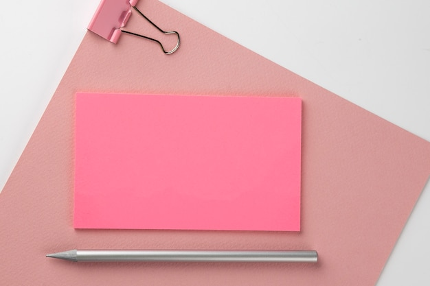Adesivo rosa su carta rosa con matita su sfondo bianco,spazio copia