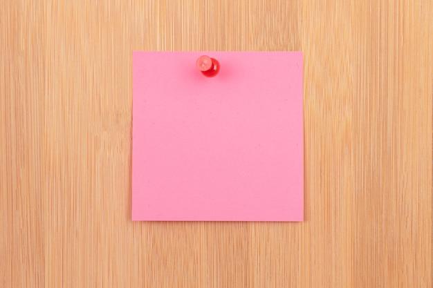 Nota adesiva rosa appuntata alla bacheca di legno