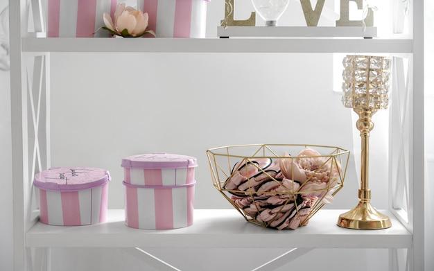 Contenitori di regali a strisce rosa con gli accessori domestici dorati sullo scaffale bianco