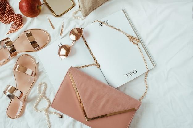 Composizione di moda donna in stile rosa con accessori femminili, bigiotteria, accessori su lino bianco a letto