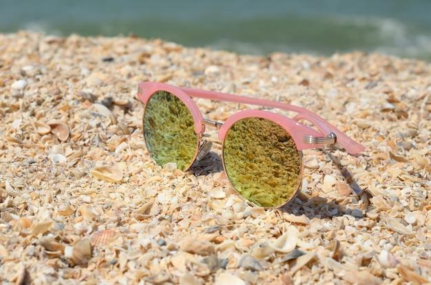 Occhiali da sole rosa contro il sole sulla sabbia della spiaggia