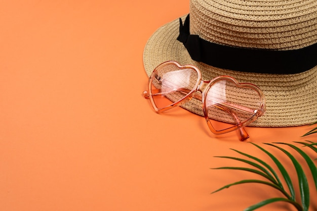 Occhiali da sole rosa e un cappello su sfondo arancione. copia spazio.