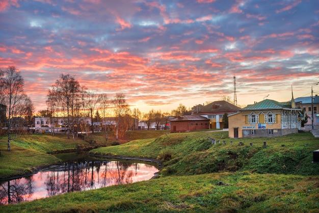 Alba rosa con riflesso nell'acqua del fiume volga a uglich e il museo della vita urbana nella mattina d'autunno. didascalia: museo della vita urbana