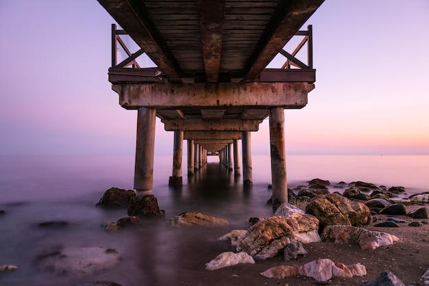 Tramonto rosa visto da sotto un vecchio pontile in legno su una spiaggia della costa del sol a marbella.