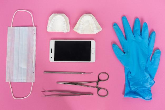 Su una superficie rosa ci sono guanti blu, uno smartphone, strumenti odontoiatrici e un calco di denti in gesso bianco