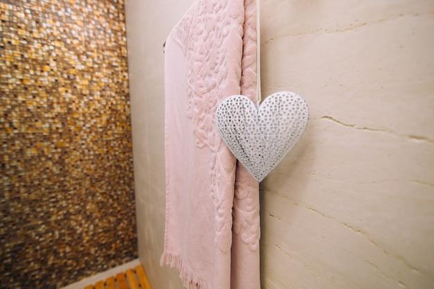 Un asciugamano rosa viene asciugato in bagno sul portasciugamani riscaldato