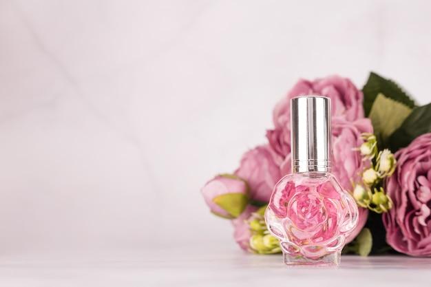 Bottiglia di profumo trasparente rosa con bouquet di peonie su fondo in marmo chiaro