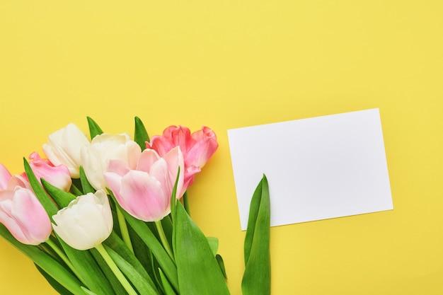 Mazzo di fiori di tulipano rosa su sfondo giallo.