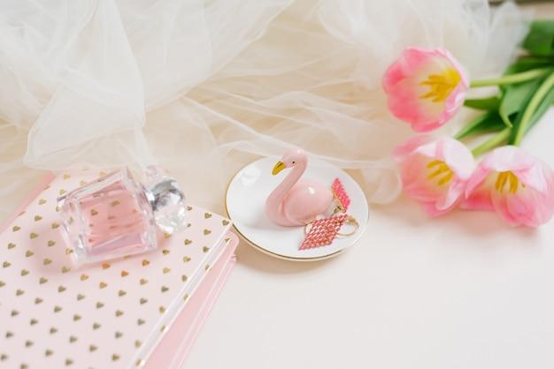 Fiori di tulipano rosa, taccuino, profumo e una figurina di fenicottero su sfondo chiaro light