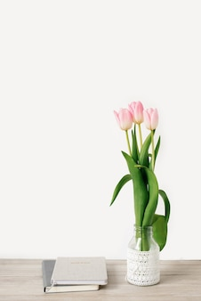 Fiori di tulipano rosa in un vaso sul tavolo e un diario con un blocco note, un muro bianco come sfondo con spazio di copia