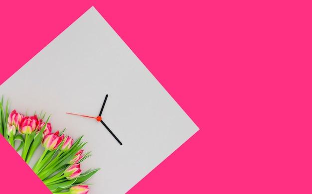 Tulipani rosa e lancette dell'orologio su uno sfondo a blocchi di colore grigio e rosa copia spazio