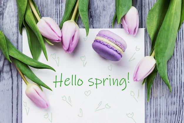 Tulipani rosa, macaron e foglio bianco su un fondo di legno grigio, ciao carta di primavera