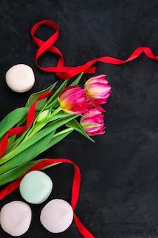 Tulipani rosa con nastro rosso a forma di numero 8 su sfondo nero