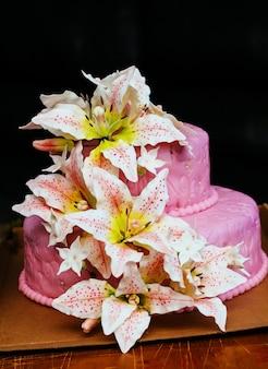 Torta nuziale rosa con fiore di giglio topper