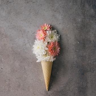 Fiori rosa e bianchi nel cono gelato sulla parete di marmo. concetto minimo. lay piatto.