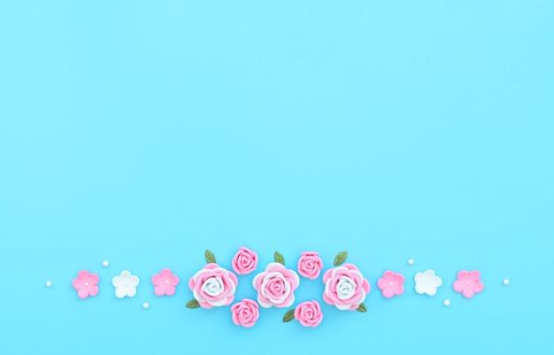 Fiori rosa e bianchi in foamiran con foglie verdi e perle bianche su sfondo blu.