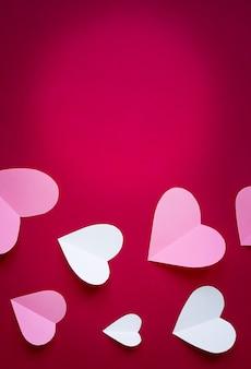 Cuori di carta rosa e bianco su sfondo rosa