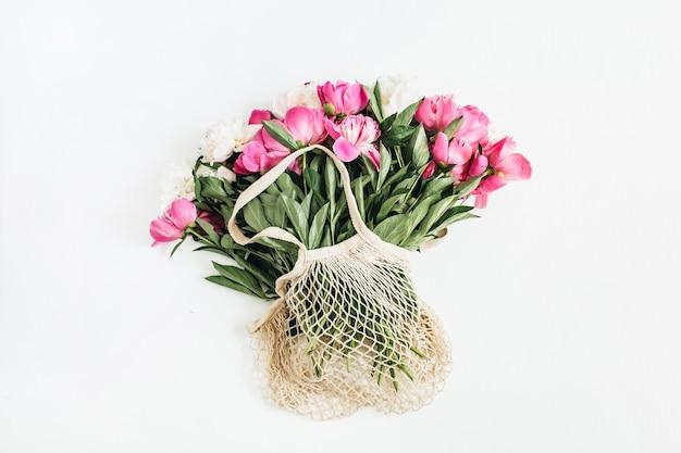 Fiori di peonia rosa e bianchi in sacchetto di stringa sulla superficie bianca