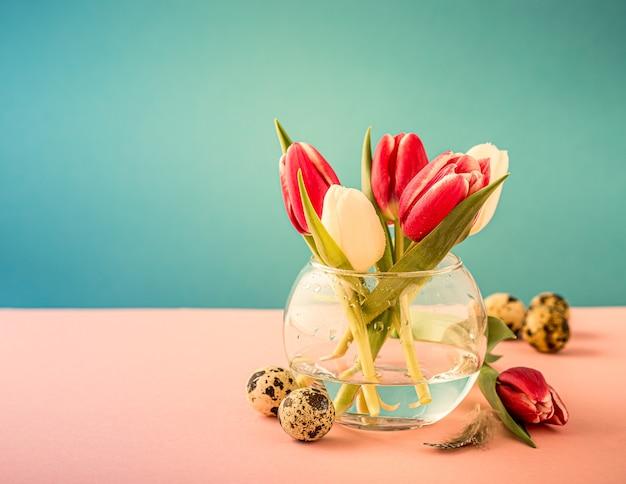 Tulipani rosa e bianchi in vasi di vetro sulla superficie blu. un regalo per la festa della donna. biglietto di auguri per la festa della mamma. copia spazio